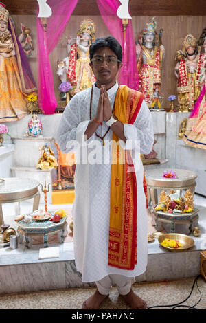Posed portrait of a teenage pandit at a youth service at the Milan Mandir Hindu temple in South Ozone Park, Queens, New York. - Stock Photo