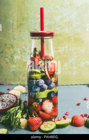 Tasty infused water in bottle with drink straw and ingredients, front view. Water Flavored with colorful fruits, berries and herbs. Summer drinks. Hea - Stock Photo