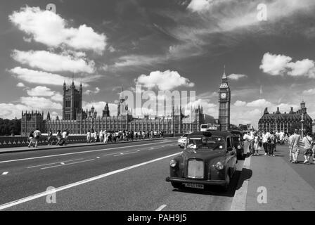 A black and white image of a London taxi cab stopped on Westminster bridge as tourists make their way to the Houses of Parliament and Big Ben - Stock Photo