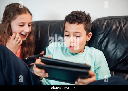 Little boy and his sister are playing on handheld game consoles at home. - Stock Photo