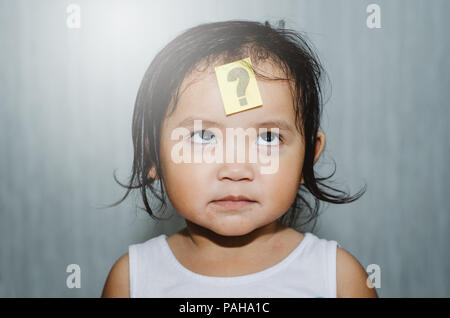 asian cute toddler looking at question mark on her forehead with funny face. child learning and growth concept - Stock Photo