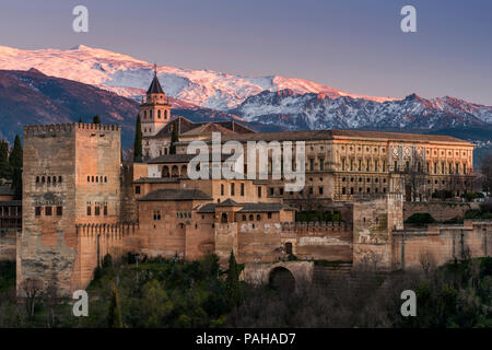 View at sunset of Alhambra palace with the snowy Sierra Nevada in the background, Granada, Andalusia, Spain - Stock Photo