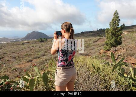 Pretty young adult traveler visits Tenerife, Canary Islands, Spain - volcanic mountains and rural area. Taking photos during vacation. - Stock Photo