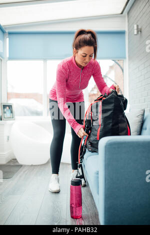 Personal trainer is getting ready to go to work from her home. She is packing a bag with sports equipment. - Stock Photo