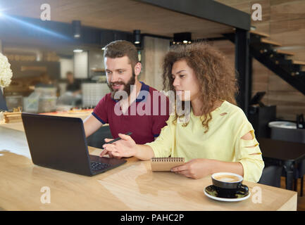 Couple of students studying in cafe using laptop. Drinking coffee, writing in notebook, looking concentrated. Wearing casual colorful clothes. Working for university's educational project. - Stock Photo