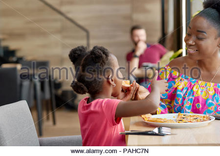Happy mother feeding child delicious pizza sitting in local restaurant. Smiling, having good mood, wonderful time together, lovely family. Other clients sitting in cafe's background. Loft interior. - Stock Photo