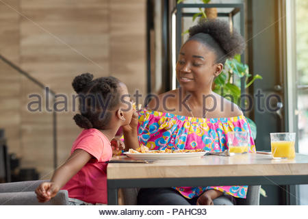 Smiling mother feeding child delicious pizza sitting in local cafe. Happy, having good mood, wonderful time together, lovely family. Other clients sitting in cafe's background. Loft interior. - Stock Photo