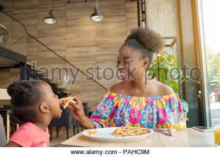 Laughing mother feeding child delicious pizza sitting in loft designed restaurant. Smiling, having good mood, wonderful time together, lovely family. Other clients sitting in cafe's background. - Stock Photo