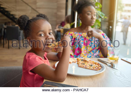 Hungry little girl eating pizza sitting near her mother in cafe. Happy, having good mood, wonderful time together, lovely family. Other clients sitting in cafe's background. Loft design interior. - Stock Photo