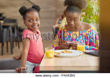 Happy smiling mother and daughter drinking orange juice, eating pizza. Mother keeping smartphone, chatting in Internet. Cute little girl looking at camera, feeling happy, spending family time. - Stock Photo