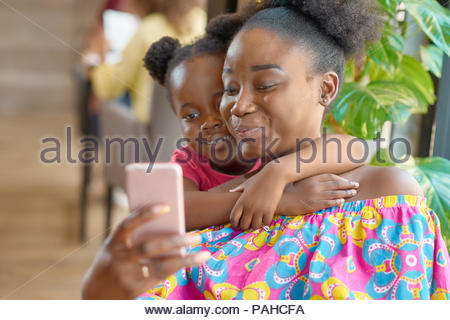 Smiling mother taking selfie with her cute little daughter. Looking at smartphone, feeling happy, satisfied, relaxed. Family hugs, lovely photo. Having good time. Sitting in cafe. - Stock Photo