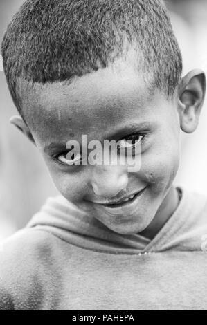 OMO VALLEY, ETHIOPIA - SEP 22, 2011: Unidentified Ethiopian cute boy smiles for the camera in Ethiopia, Sep.22, 2011. People in Ethiopia suffer of pov - Stock Photo
