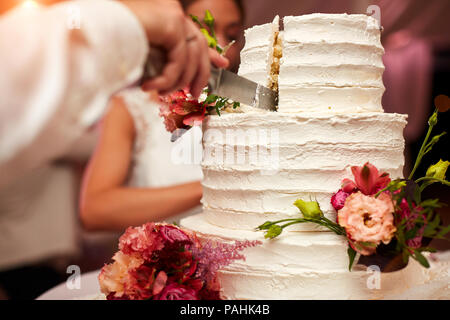 groom cuts the wedding cake - Stock Photo