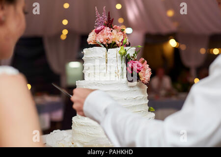 bride and groom cut wedding cake - Stock Photo