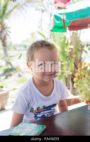 little boy is sitting at a table next to a book and smiling. - Stock Photo