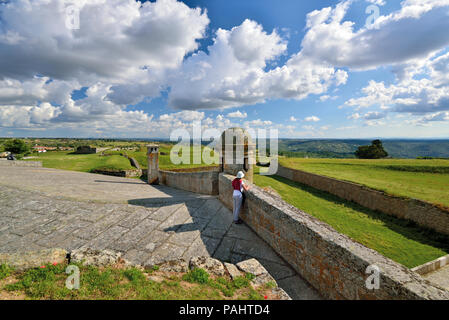 Woman enjoying view from fortress walls over a wide green land and dramatic moving clouds - Stock Photo
