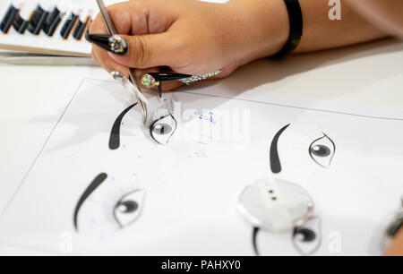 selective focus practicing and training eyelash extension on paper in class - Stock Photo