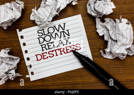 Text sign showing Slow Down Relax De Stress. Conceptual photo Have a break reduce stress levels rest calm Paper lumps laid randomly around white notep - Stock Photo