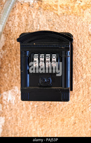 Old code padlock in house shape on textured wall - Stock Photo