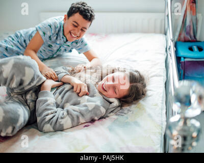 Little boy and his older sister are playfighting on a bed at home. - Stock Photo