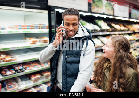 Little girl is shopping with her father. He is pushing a trolley and talking on his phone. - Stock Photo