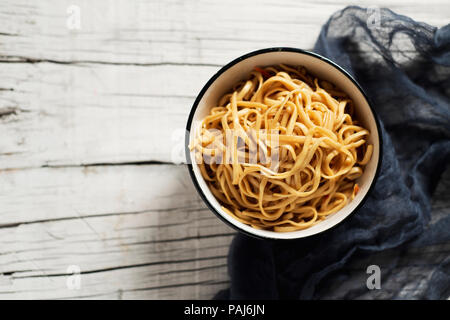 high angle view of a white ceramic bowl with yakisoba noodles, with vegetables and yakisoba sauce, on a white rustic wooden table with some blank spac - Stock Photo