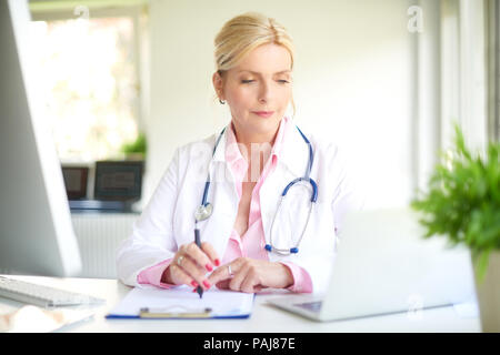 Smiling elderly female doctor sitting at doctor's room and using computer and laptop while writing diagnosis. - Stock Photo