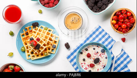Photo of Viennese waffles, oatmeal, coffee, raspberries, strawberries, gooseberries - Stock Photo