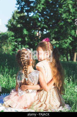 Toned portrait of Two Happy little girls embracing  and spending time at sunny summer park - Stock Photo