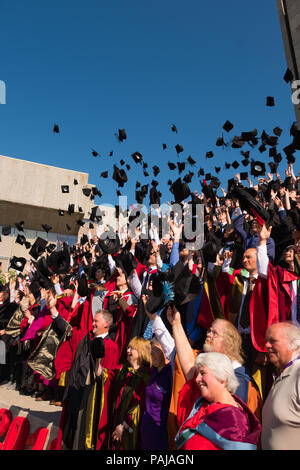 Higher Education in the UK: Students graduating from Aberystwyth university, throwing their caps and mortar boards in the air for their traditional graduation photograph. July 2018 - Stock Photo