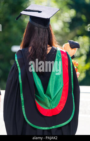Higher Education in the UK: Rear vew of a female student graduating from Aberystwyth university, in her traditional mortar board and black academic gown. July 2018 - Stock Photo