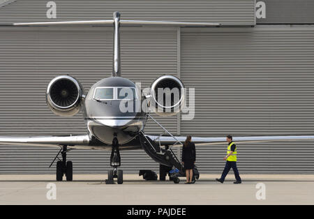 a man wearing a yellow tabard and a stewardess standing by the airstairs of a Gama Aviation Gulfstream 4SP parked with the TAG hangar behind - Stock Photo