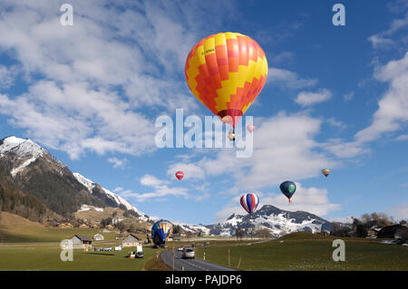 a Kubicek BB-30 hot-air balloon flying with other hot-air balloons, cars, road, chalets, trees, mountains and snow behind - Stock Photo