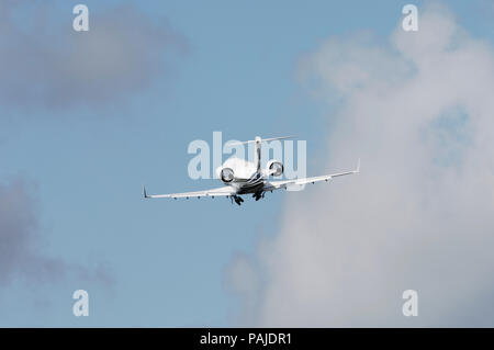 Bombardier Challenger CL-601-3A climbing out after take-off with the undercarriage retracting - Stock Photo