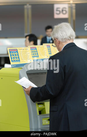 passengers checking-in at British Airways self-service check-in kiosks managed by Aviance in Manchester Airport Terminal3, IBM series N kiosks - Stock Photo