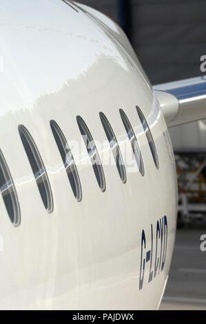 windows on British Airways BA CityFlyer Embraer 170-100STD parked - Stock Photo
