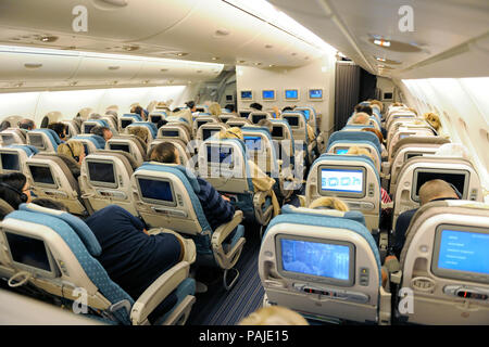 passengers sitting in economy-class cabin seats Singapore ...