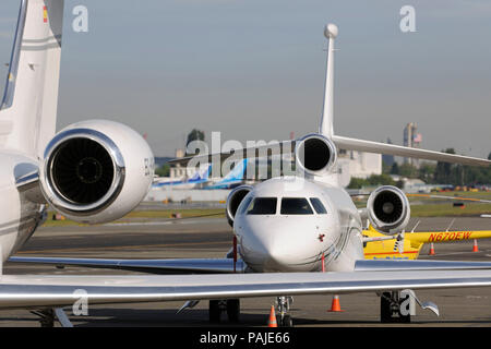 Dassault Falcon 7X and tail-fin of Gulfstream 5 parked with tail-fins of Boeing 787 Dreamliners behind - Stock Photo