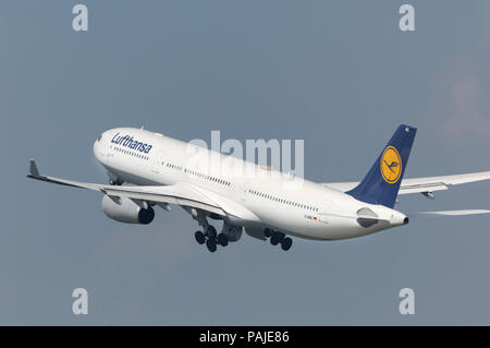 Lufthansa Airbus A330-300 climbiong out after take-off with undercarriage retracting - Stock Photo