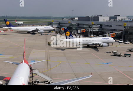 Lufthansa Airbus A320-200 with A330-300 parked at the terminal, Air Malta A320-200 taxiing behind - Stock Photo