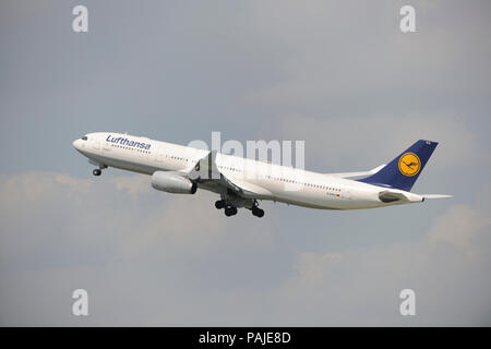 Lufthansa Airbus A330-300 climbing out after take-off with undercarriage retracting - Stock Photo