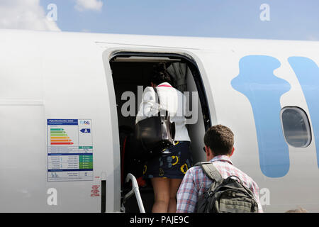 passengers with carry-on bags boarding a Flybe Bombardier DHC-8 Q400 parked - Stock Photo
