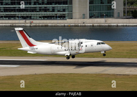 Scot Airways Dornier Do-328-100 landing at London City with Newham Docklands building behind - Stock Photo