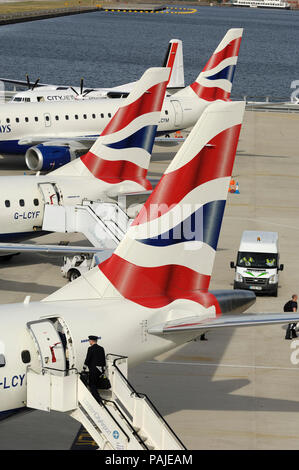 tail-fins of British Airways BA CityFlyer Embraer 170, 190s and CityJet Fokker F-50 parked in a row at London City - Stock Photo