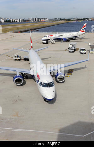 British Airways BA CityFlyer Embraer 190LR taxiing with Embraer 190 parked behind at London City - Stock Photo