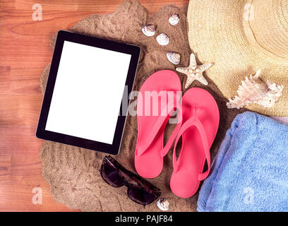tablet computer and flip flops on beach sand Stock Photo