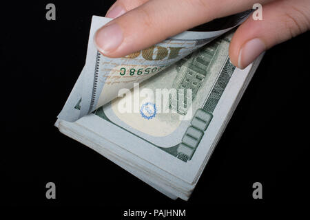 Hand holding American dollar  banknotes isolated on black background - Stock Photo