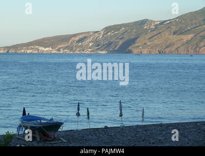 A wood fisher boat and umbrellas on the beach sand with serene sea water and mountains on the background. No people. - Stock Photo