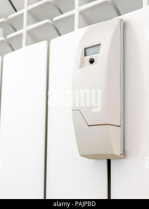 Smart heat meter mounted on house radiator - Stock Photo