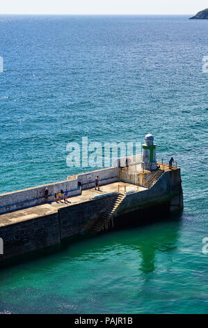 People fishing on the outer harbour at Laxey, Isle of Man - Stock Photo